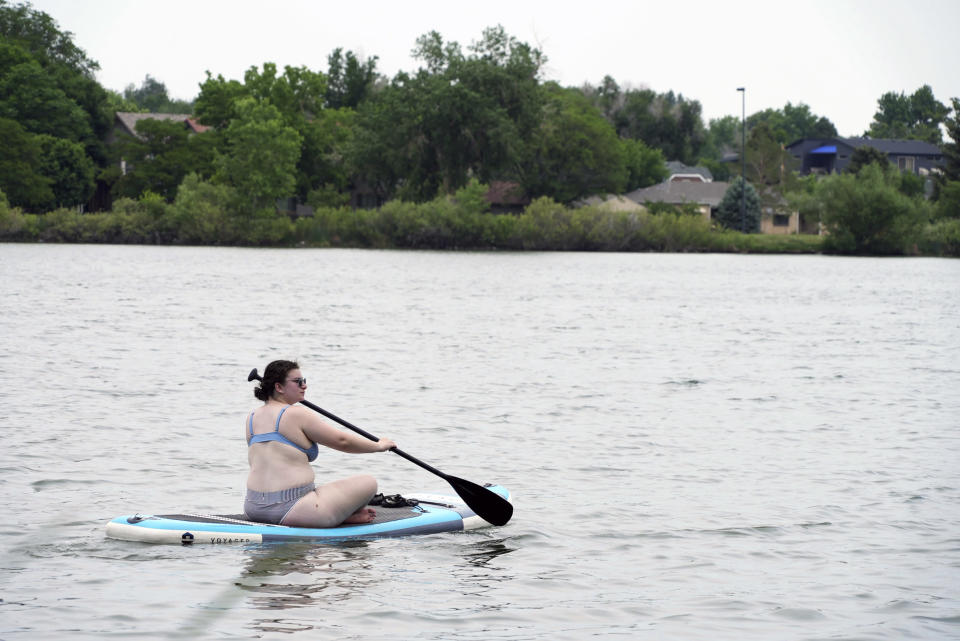 Bekka Hamburg paddle boards on Sloan's Lake in Denver on Wednesday, June 16, 2021. A heat wave continues to hover over the western U.S., pushing the temperature to 99 degrees in Denver. Hamburg, visiting from Indianapolis, said she rented the paddle board a week ago when she saw the forecast. (AP Photo/Brittany Peterson)