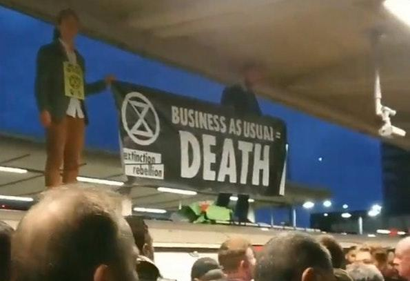 "The protesters were seen holding a banner reading ""Business as usual = death"". (PA)"