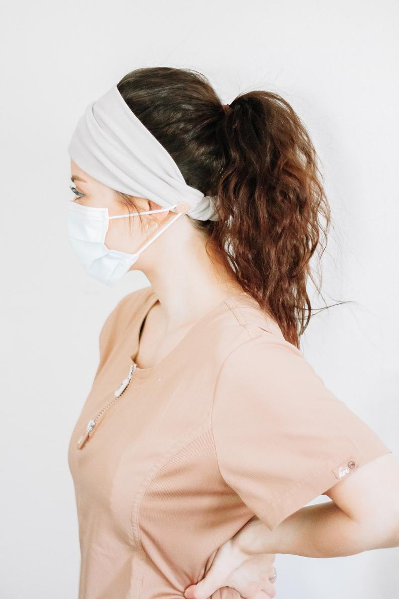 "<h2>Headband With Buttons</h2> <br><a href=""https://www.refinery29.com/en-us/2020/04/9662080/nurse-n95-bruises-face-mask"" rel=""nofollow noopener"" target=""_blank"" data-ylk=""slk:Face masks can often cause irritation"" class=""link rapid-noclick-resp"">Face masks can often cause irritation</a> behind the ears, where the elastic bands tend to dig into the skin. These inventive headbands have buttons on either side; wrap the elastic around those to save your ears.<br><br><strong>PhoenixAndHawke</strong> Headband With Buttons, $, available at <a href=""https://go.skimresources.com/?id=30283X879131&url=https%3A%2F%2Fwww.etsy.com%2Flisting%2F792449033%2Fbest-selling-headband-with-buttons-for"" rel=""nofollow noopener"" target=""_blank"" data-ylk=""slk:Etsy"" class=""link rapid-noclick-resp"">Etsy</a><br>"