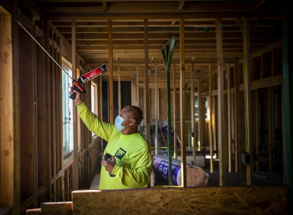 Construction worker Jose Hernandez seals windows at an all-electric housing development being built in San Bernardino.