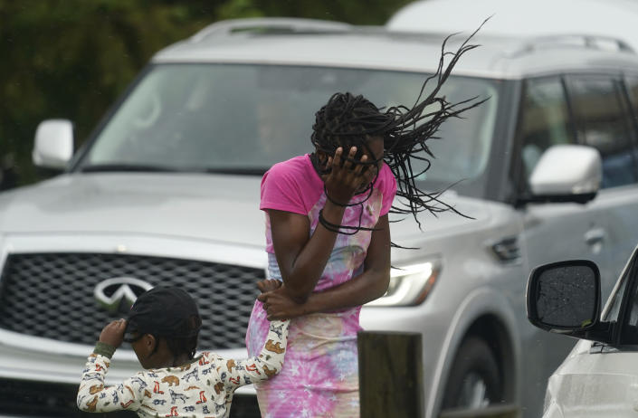 A woman and child stand near cars as they block their faces from the wind and rain.