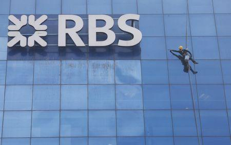 Worker cleans the glass exterior next to the logo of RBS (Royal Bank of Scotland) bank at a building in Gurugram
