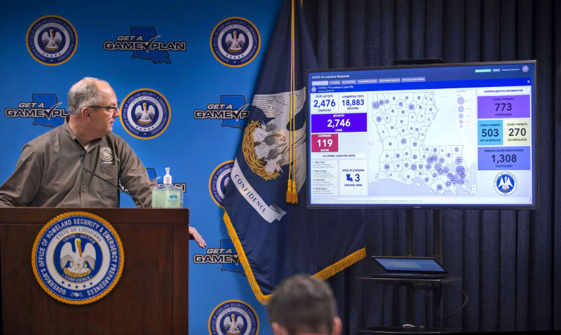 Louisiana Gov. John Bel Edwards looks at a monitor displaying the state's evolving novel coronavirus COVID-19 situation, at the start of a press conference, Friday, March 27, 2020 at the Governor's Office of Homeland Security & Emergency Management in Baton Rouge, La. (Travis Spradling/The Advocate via AP, Pool)