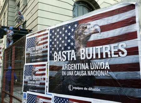 """Construction workers work near posters that read """"Enough vultures, Argentina united for a national cause"""" in Buenos Aires"""