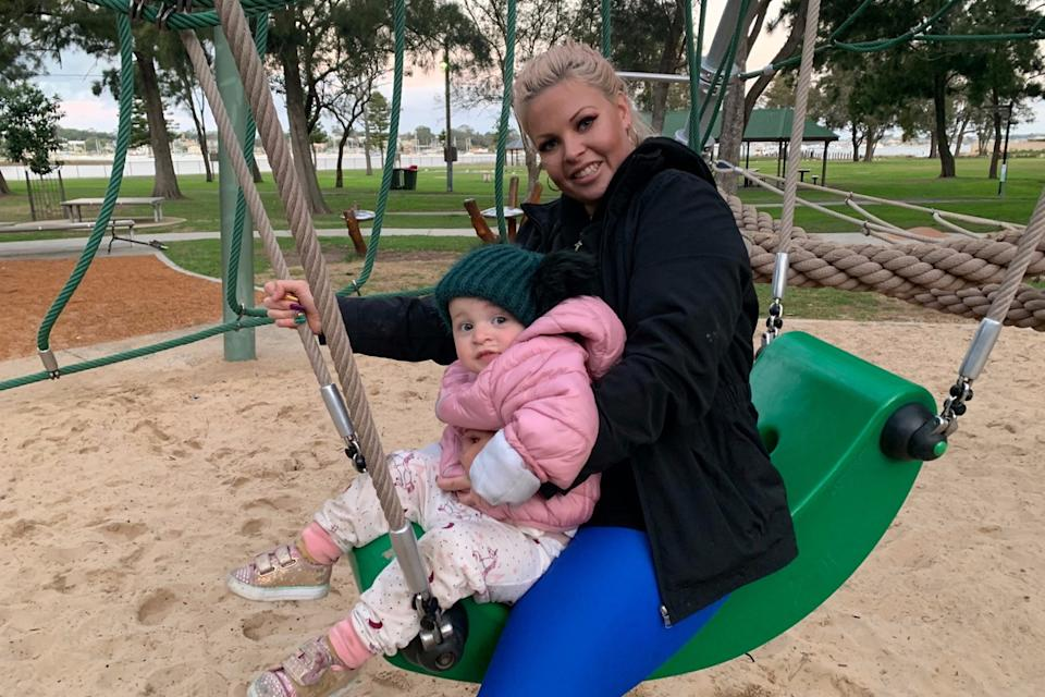 Lola and Elle Wilkinson on a swing set while bundled up in warm jackets.