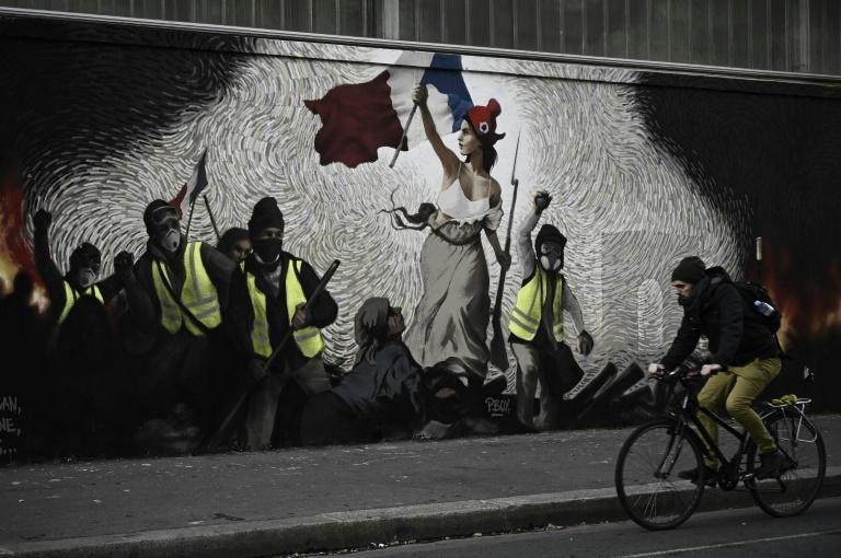 A mural by street artist PBOY depicts 'yellow vest' protesters inspired by a painting by Eugene Delacroix