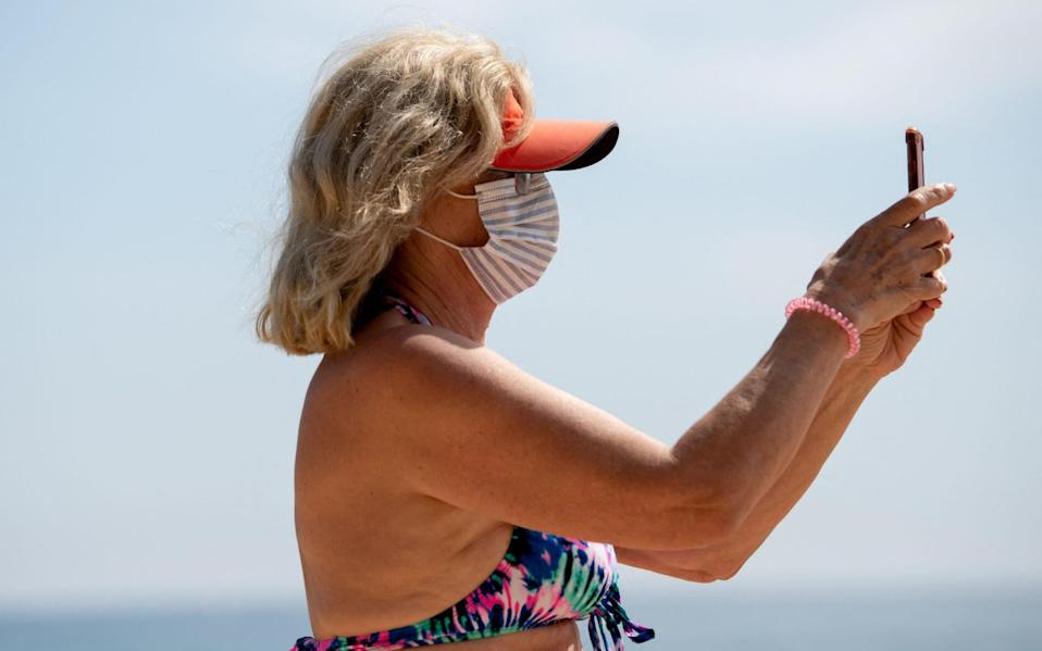 woman on beach in face mask - Josep Lago/AFP