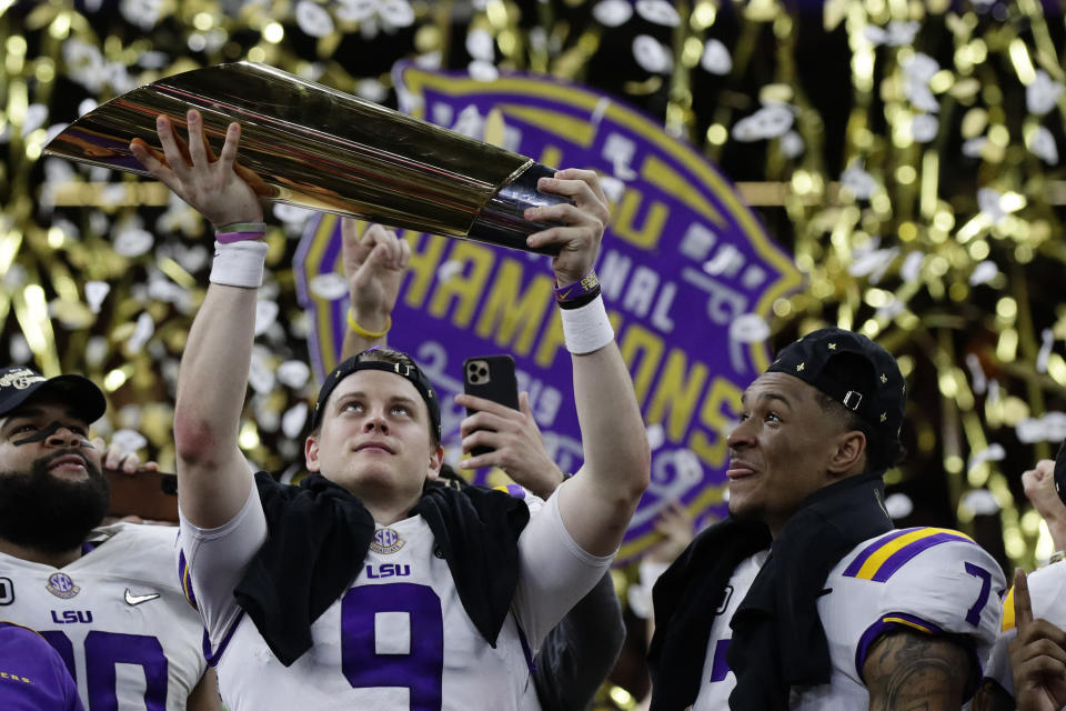 LSU quarterback Joe Burrow holds the trophy as safety Grant Delpit looks on after a NCAA College Football Playoff national championship game against Clemson, Monday, Jan. 13, 2020, in New Orleans. LSU won 42-25. (AP Photo/Sue Ogrocki)