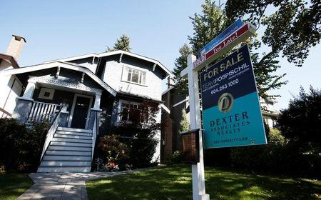 A real estate for sale sign is pictured in front of a home in Vancouver