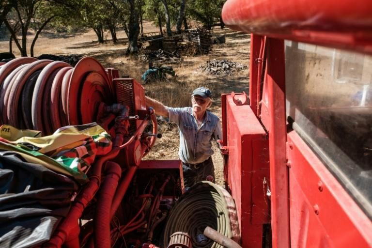Randy Dunn checks the hose on a fire truck he has purchased to protect his vinyard from California wildfires (AFP/Nick Otto)