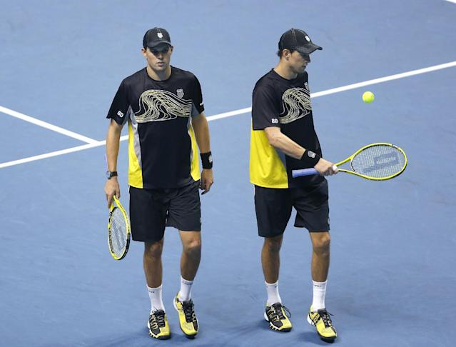 Mike Bryan of United States, left with playing partner and twin brother Bob Bryan of United States talk together as they walk back to the base line and prepare to serve to Fernando Verdasco of Spain and David Marrero of Spain during the final of the ATP World Tour Finals at the O2 Arena in London, Monday, Nov. 11, 2013. (AP Photo/Kirsty Wigglesworth)