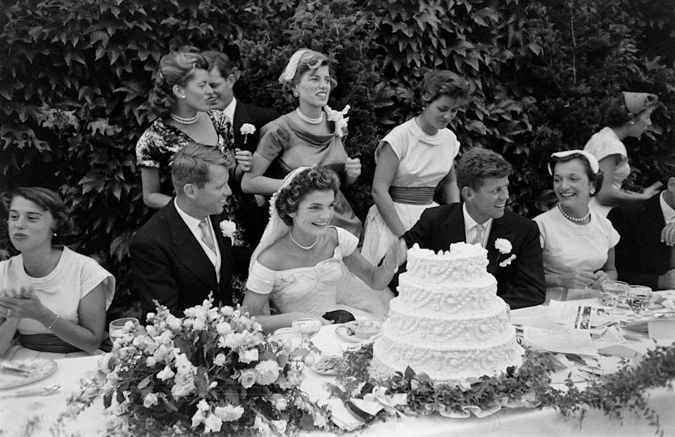 <p>Surrounded by the Kennedy clan, the newly wed Mr. and Mrs. Kennedy admire their wedding cake. The couple married earlier that day at St. Mary's Roman Catholic Church and had an outdoor reception at the Jackie's Rhode Island estate. </p>