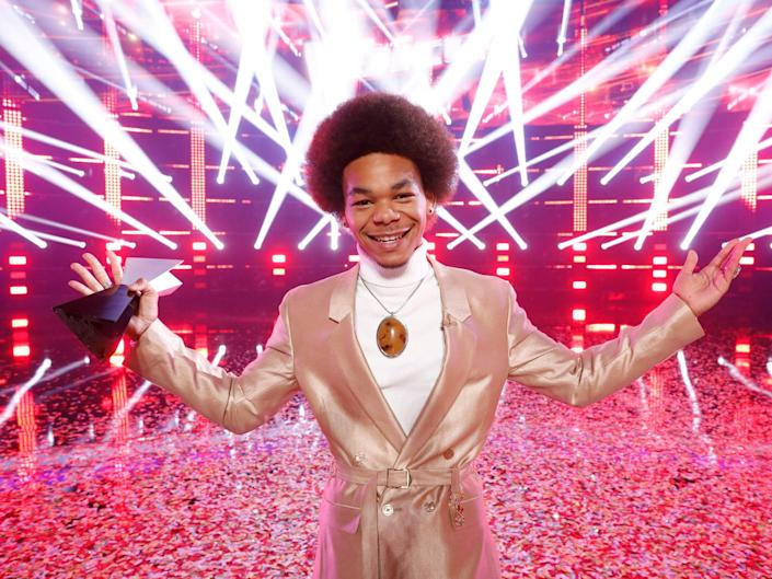 """Cam Anthony holding his winning trophy in front of a red, strobe-light background on """"The Voice"""""""