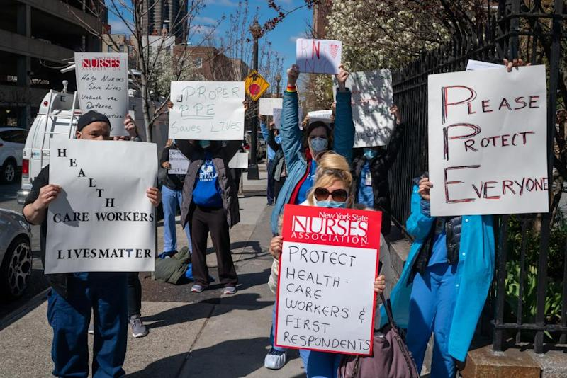 Nurses hold signs during a demonstration for increased personal protection equipment outside Montefiore Hospital in the Bronx borough of New York, U.S., on Thursday, April 2, 2020. Health-care workers and others essential to the Covid-19 fight say they're increasingly frustrated that they're being sent into a deadly battle without the protective gear they need for themselves and their patients.