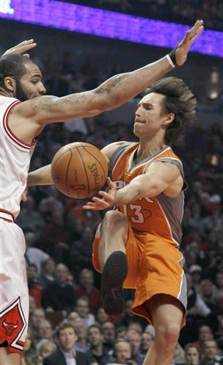 Phoenix Suns guard Steve Nash (13) passes under the arm of Chicago Bulls forward Carlos Boozer during the first half of an NBA basketball game Tuesday, Jan. 17, 2012, in Chicago. (AP Photo/Charles Rex Arbogast)