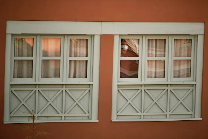 A man looks out of a window at a quarantined hotel on the Canary island of Tenerife, Spain, on February 26.