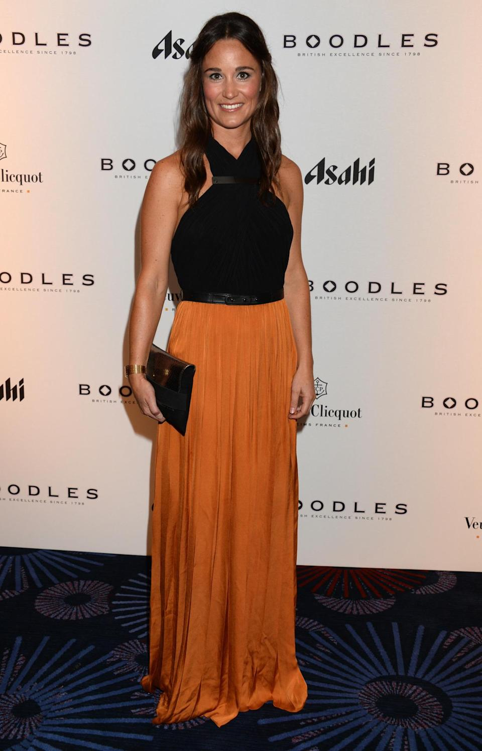 <p>Catherine Deane was Pippa's designer of choice at a ball in 2013. Boasting a burnt orange maxi skirt and a black halter neck bodice, the form-fitting number was a great choice for the brunette. <i>[Photo: Getty]</i> </p>