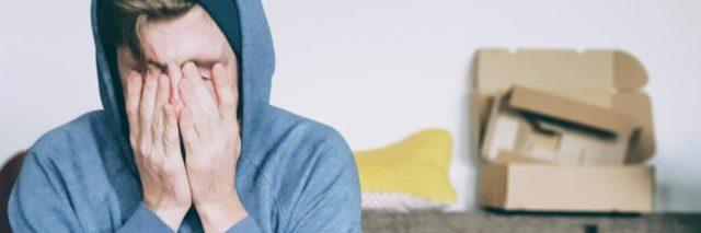 photo of man in hoodie sitting on sofa with his hands over his eyes, looking overwhelmed