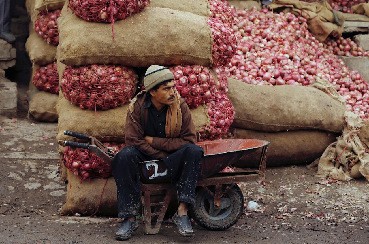 A labourer sits in a wheelbarrow near the sacks of onions as he waits for customers at a wholesale market in Islamabad, Pakistan December 11, 2018.  PREUTERS/Faisal Mahmood