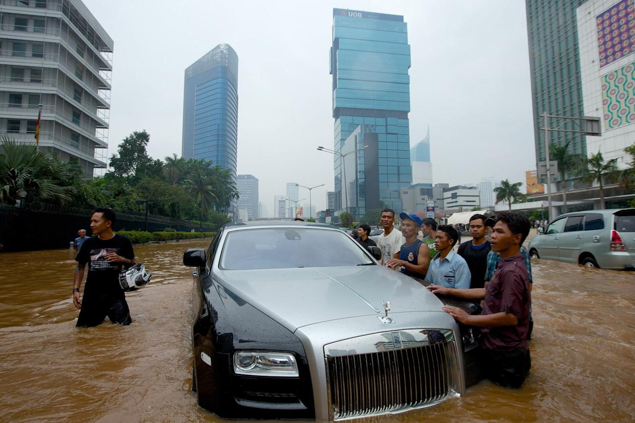 JAKARTA, INDONESIA - JANUARY 17:  A Rolls Royce is stranded in floodwater in Jakarta's central business district on January 17, 2013 in Jakarta, Indonesia.  Thousands of Indonesians were displaced and the capital was covered in many key areas in over a meter of water after days of heavy rain. (Photo by Ed Wray/Getty Images)