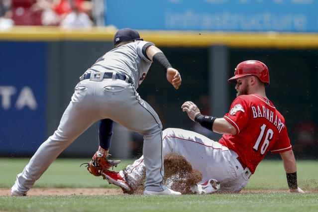 Detroit Tigers shortstop Jose Iglesias, left, tags out Cincinnati Reds catcher Tucker Barnhart (16) on a steal attempt in the first inning of a baseball game, Wednesday, June 20, 2018, in Cincinnati. (AP Photo/John Minchillo)