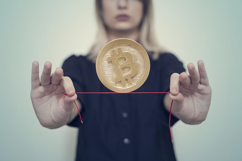 Woman's hands hold Gold Bitcoin on a thread