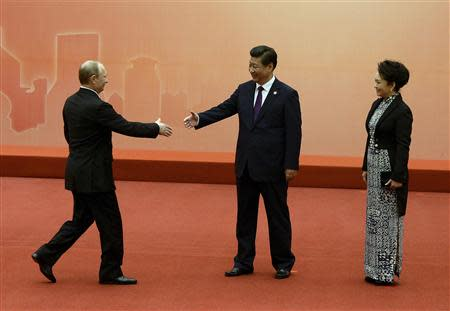 Russian President Vladimir Putin (L) is greeted by the Chinese President Xi Jinping (C) and his wife Peng Liyuan before the group photo event at the fourth Conference on Interaction and Confidence Building Measures in Asia (CICA) summit in Shanghai May 20, 2014. REUTERS/Mark Ralston/Pool