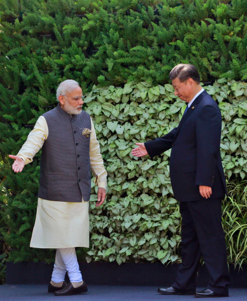 """FILE - In this Oct. 16, 2016 file photo, Indian Prime Minister Narendra Modi, left, and Chinese President Xi Jinping, gesture towards each other after a group photo of BRICS leaders at the start of the Summit in Goa, India. India's Ministry of External Affairs said Wednesday, Oct. 9, 2019, that Xi and Modi would meet for a second informal summit in the southern coast city of Chennai on Oct. 11 and 12 to """"exchange views on deepening"""" the two countries' development. (AP Photo/Anupam Nath, File)"""