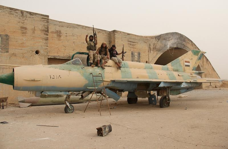 Members of Al-Qaeda's Syrian affiliate and its allies sit on top of a former Syrian army MiG-21 fighter jet at the Abu Duhur airbase in this September 9, 2015 file photo