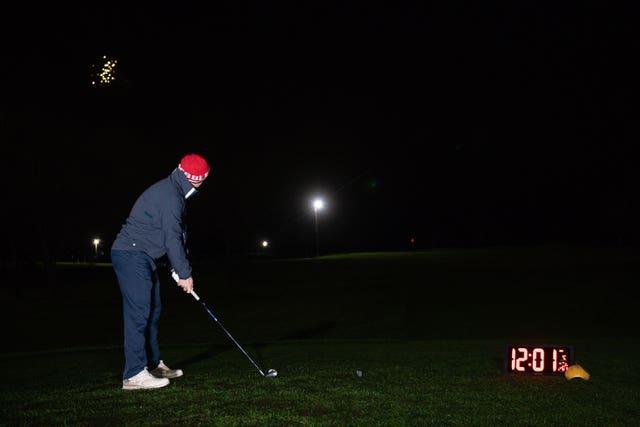 Richard Silk takes the first tee shot with a neon coloured ball whilst under floodlights at Morley Hayes Golf centre