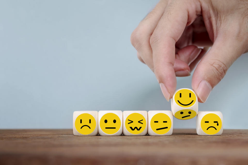 Hand Changing with smile emoticon icons face on Wooden Cube , hand flipping unhappy turning to happy symbol
