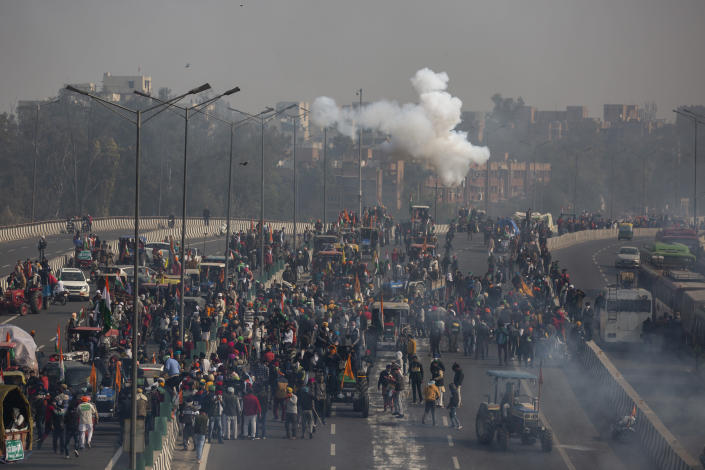 Indian police fire tear gas shells towards protesting farmer as they march to the capital breaking police barricades during India's Republic Day celebrations in New Delhi, India, Tuesday, Jan.26, 2021. Tens of thousands of farmers drove a convoy of tractors into the Indian capital as the nation celebrated Republic Day on Tuesday in the backdrop of agricultural protests that have grown into a rebellion and rattled the government. (AP Photo/Altaf Qadri)
