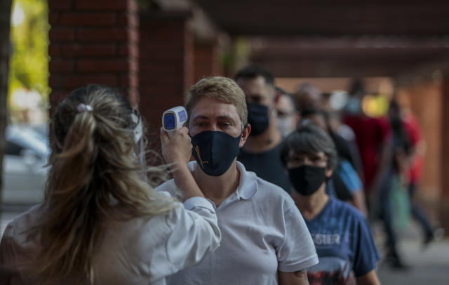 SAO PAULO, BRAZIL - JUNE 11: A customer wearing a face mask has his temperature measured during the first day of open stores at a shopping mall amidst the coronavirus (COVID-19) pandemic on June 11, 2020 in Sao Paulo, Brazil. Establishments in the city of Sao Paulo will be able to operate only 4 hours a day, between 11 am and 3 pm, and must follow hygiene standards. (Photo by Miguel Schincariol/Getty Images)
