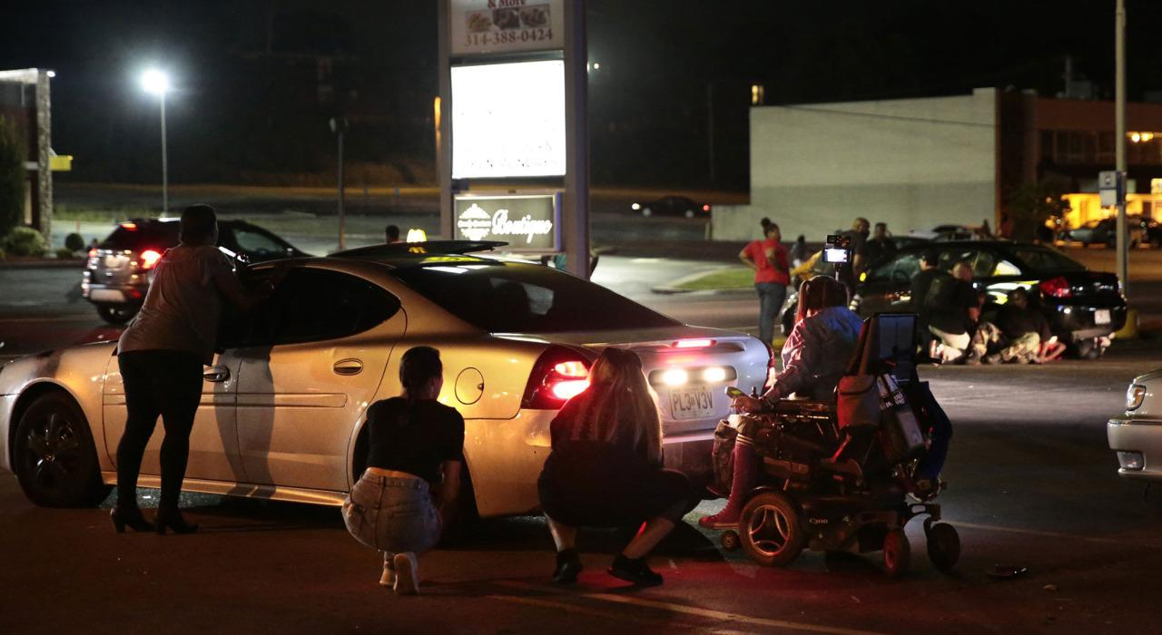 <p>Protesters hide behind cars after shots were fired Tuesday, Aug. 9, 2016, in Ferguson, Mo., during a demonstration on the second anniversary of Michael Brown's death. (Robert Cohen/St. Louis Post-Dispatch via AP)</p>