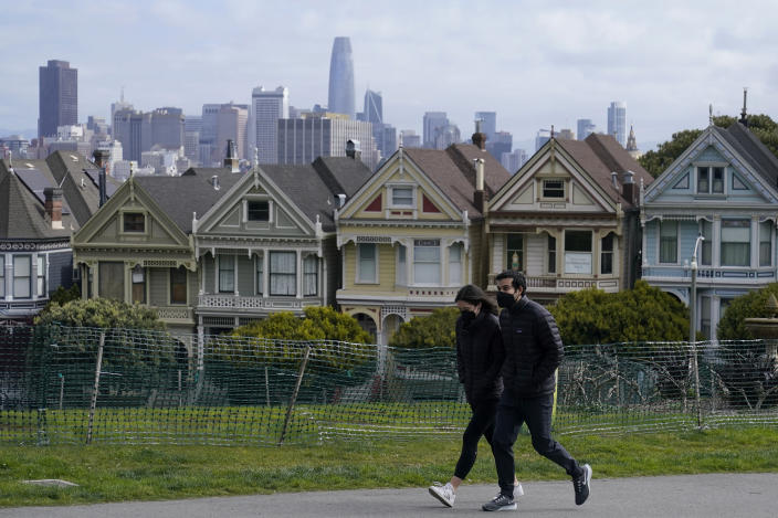 """FILE - In this March 13, 2021, file photo, people wearing masks walk along at path in front of the """"Painted Ladies,"""" a row of historical Victorian homes, and the San Francisco skyline at Alamo Square Park during the coronavirus pandemic in San Francisco. California will offer six """"dream vacation"""" incentives to spur more people to get coronavirus vaccinations, California Gov. Gavin Newsom said Monday, June 14, 2021, on the eve of the state's awarding of $15 million in cash prizes. Newsom spoke in San Francisco, site of one of the six vacation packages offered by various providers through Visit California, the state's quasi-independent travel promotion arm. (AP Photo/Jeff Chiu, File)"""