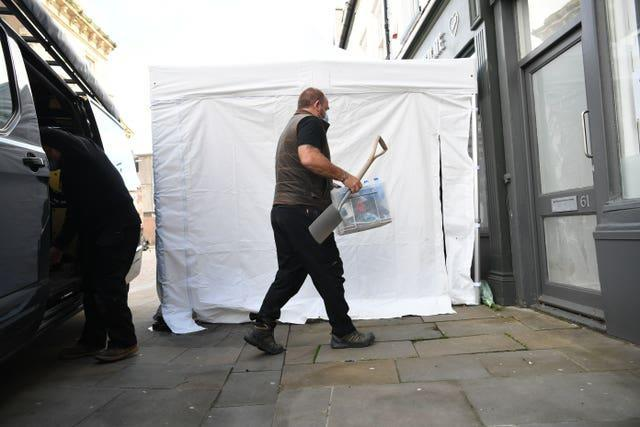 Contractors unload equipment into the Clean Plate cafe in Southgate Street, Gloucester as excavation work for missing Mary Bastholm got underway (Ben Birchall/PA)
