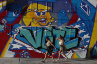 People walk past an election-themed mural by artist Mr. Ewok One, outside the Museum of Graffiti in Wynwood, Miami, Friday, Oct. 30, 2020.(AP Photo/Rebecca Blackwell)