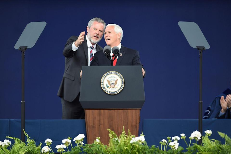 Liberty President Jerry Falwell Jr., left, speaks with Vice President Mike Pence at the Liberty University commencement ceremony in Lynchburg, Va., on Saturday, May 11, 2019.