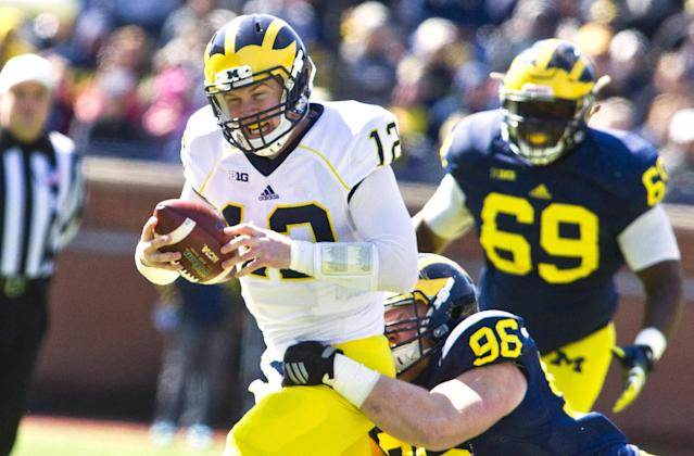 "Michigan quarterback <a class=""link rapid-noclick-resp"" href=""/ncaaf/players/251039/"" data-ylk=""slk:Alex Malzone"">Alex Malzone</a> (12) is tackled by defensive lineman <a class=""link rapid-noclick-resp"" href=""/nfl/players/30251/"" data-ylk=""slk:Ryan Glasgow"">Ryan Glasgow</a> (96) during a spring NCAA college football game in Ann Arbor, Mich., Saturday, April 4, 2015. (AP Photo/Tony Ding)"