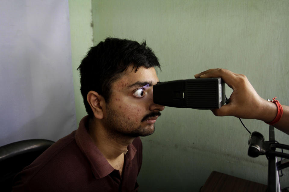 FILE- In this May 16, 2012 file photo, an Indian man gets his retina scanned to register for Aadhar, India's unique identification project, in Kolkata, India. A U.S.-based private cybersecurity company said Wednesday, Sept. 22, 2021, it has uncovered evidence that an Indian media conglomerate, a police department and the agency responsible for the country's national identification database have been hacked, likely by a state-sponsored Chinese group. (AP Photo/Bikas Das, File)