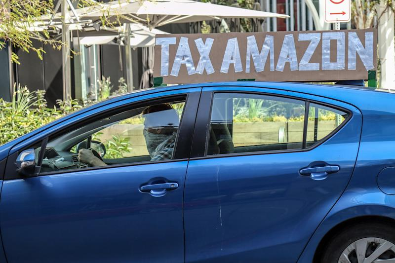 SEATTLE, UNITED STATES - MAY 01, 2020: A vehicle with a placard saying, 'tax Amazon' during the demonstration. A caravan of autos and bicyclists encircle Amazon headquarters demonstrating in support of city council member, Kshama Sawant's proposal to impose new taxes on Amazon and other large businesses, to fund COVID-19 relief and other programs.- PHOTOGRAPH BY Toby Scott / Echoes Wire/ Barcroft Studios / Future Publishing (Photo credit should read Toby Scott / Echoes Wire/Barcroft Media via Getty Images)