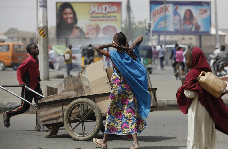 A boy pushes a cart with garbage past Muslim women on a street in Kano, Nigeria, Sunday, March. 10, 2013. The United Kingdom's military says its warplanes recently spotted in Nigeria's capital city were there to move soldiers to aid the French intervention in Mali, not to rescue kidnapped foreign hostages. The Ministry of Defense said Sunday that the planes had ferried Nigerian troops and equipment to Bamako, Mali. An Islamic extremist group in Nigeria called Ansaru partially blamed the presence of those planes as an excuse for claiming Saturday that it killed seven foreign hostages it had taken. ( AP Photo/Sunday Alamba)