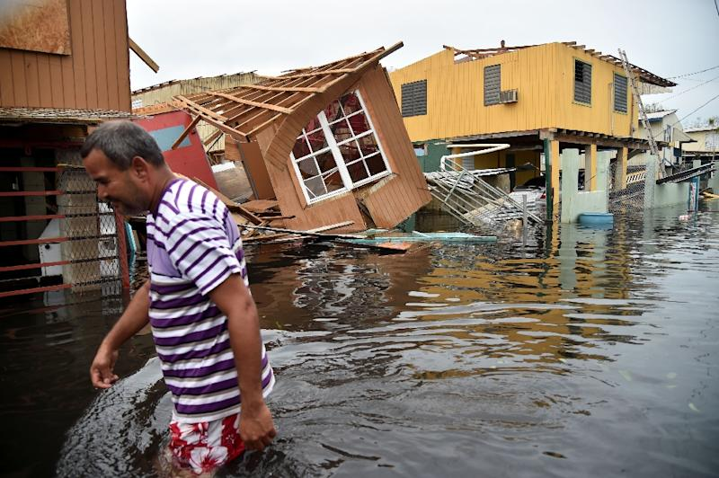 A man walks past destroyed homes in Catano, Puerto Rico, on September 21, 2017 in the wake of Hurricane Maria (AFP Photo/HECTOR RETAMAL)