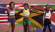 Elaine Thompson-Herah, of Jamaica, the gold medal winner celebrates after the final of the women's 200-meter with Christine Mboma, of Namibia, silver, and Gabrielle Thomas, of United States, bronze, at the 2020 Summer Olympics, Tuesday, Aug. 3, 2021, in Tokyo, Japan. (AP Photo/Charlie Riedel)