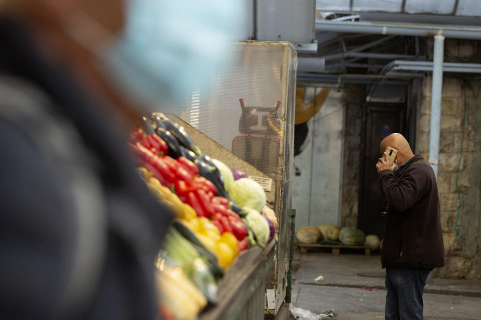 A man in a protective mask passes another man talking on his mobile phone at the Mahane Yehuda market in Jerusalem, Wednesday, Dec. 23, 2020. In the early days of the pandemic, a panicked Israel began using a mass surveillance tool on its own people, tracking civilians' mobile phones to halt the spread of the coronavirus. But months later, the tool's effectiveness is being called into question and critics say its use has come at an immeasurable cost to the country's democratic principles. (AP Photo/Maya Alleruzzo)