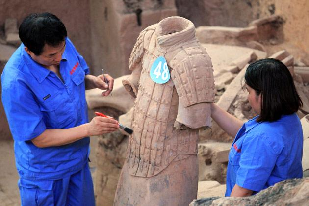 This picture taken on June 9, 2012 shows Chinese archaeologists at work in the extended excavation of the Pit One of the Terracotta Warriors and Horses Museum in Xian, carefully uncovering using delicate equipment to help preserve the detailed work in their original production more than 2,000 years ago, of the latest terracotta warrior find in Xian, China's Shaanxi province. Excavations in China have unearthed a stunning new collection of 2,000-year-old terracotta warriors and hundreds of other artefacts, as Chinese archaeologists unveiled 120 new terracotta warriors at the Qin Shihuang Unesco World Heritage site in Shaanxi province.