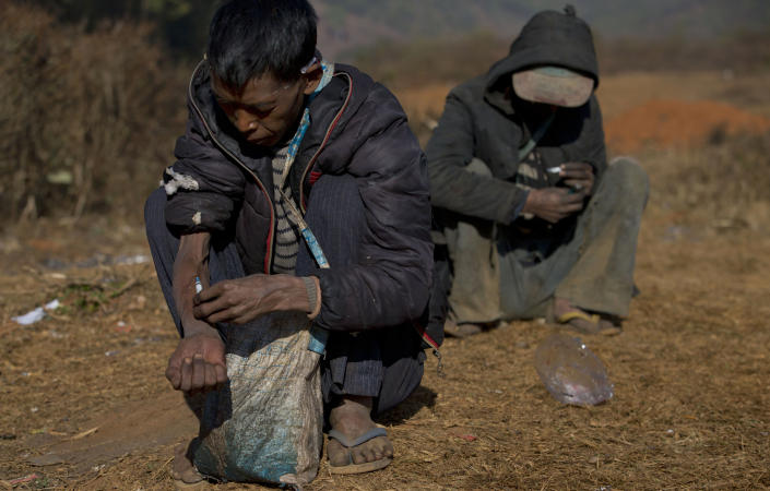 In this Jan 28, 2014 photo, addicts use needles at a cemetery in Nampatka village, northeastern Shan State, Myanmar. Every morning, more than 100 heroin and opium addicts descend on the graveyard to get high. Some junkies lean on white tombstones, tossing dirty needles and syringes into the dry, golden grass. Others squat on the ground, sucking from crude pipes fashioned from plastic water bottles. (AP Photo/Gemunu Amarasinghe)