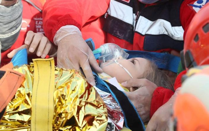 Rescue workers carry four-year-old Ayda Gezgin out from a collapsed building, four days after after an earthquake near the Turkish city of Izmir - AFAD