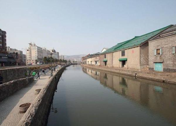 Otaru Canal viewed from Asakusa Bridge, a popular tourist attraction in Otaru, Hokkaido. Otaru Warehouse No. 1 is the fourth warehouse from the front