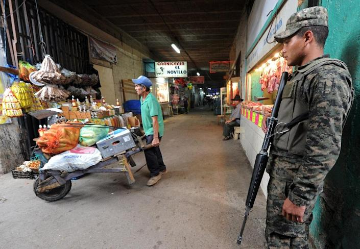 """A soldier guards Las Americas market in Tegucigalpa, where some vendors have had to leave their businesses due to a """"war tax"""" required by the so-called """"mara"""" gangs (AFP Photo/Orlando Sierra)"""